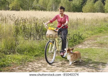 Beautiful girl on the bike and a corgi dog - stock photo