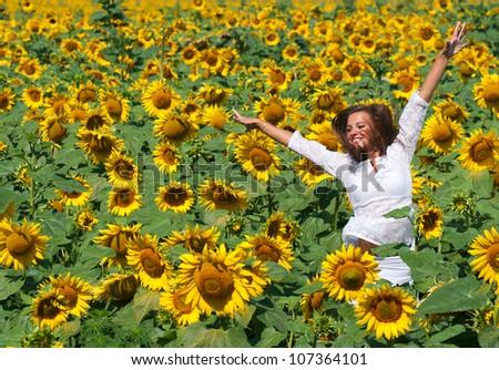 Beautiful girl on the field of sunflowers - stock photo