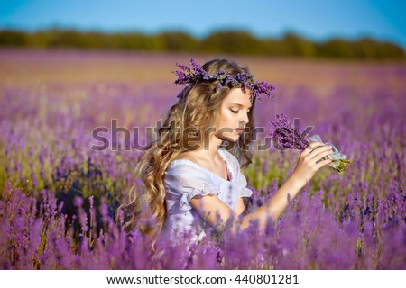 Beautiful girl on the lavender field. Girl with long hair collects lavender - stock photo