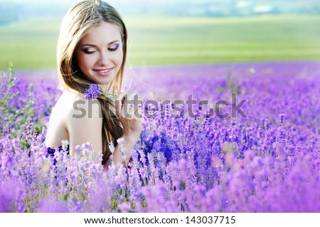 Beautiful girl on the lavender field. Young woman collects lavender in a basket