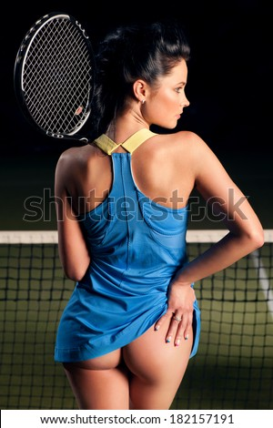Beautiful girl on the tennis court with racket in hand - stock photo