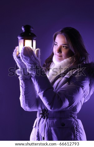 beautiful girl on winter snow with lantern