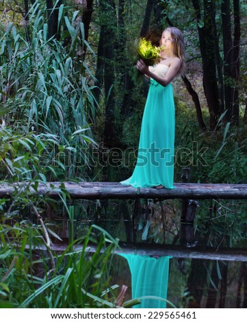 beautiful girl  on wooden bridge over the river  - stock photo