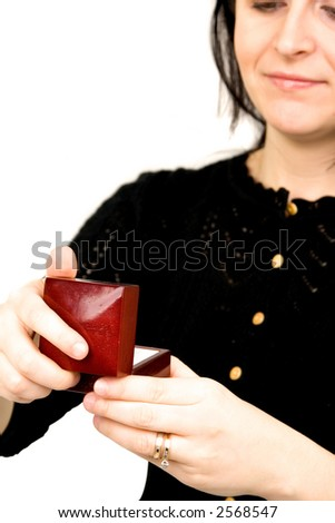 beautiful girl opening a gift isolated on a white background. Focus is on the gift - stock photo