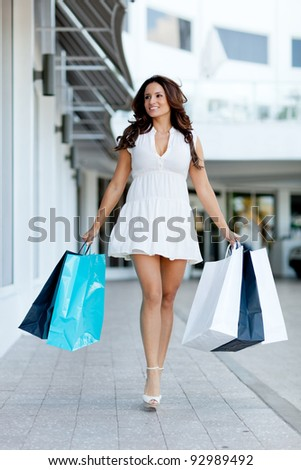 Beautiful girl out shopping holding bags at the mall - stock photo