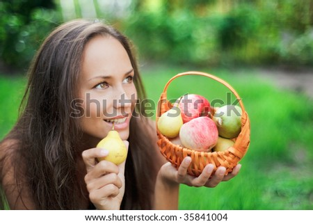 Beautiful girl outdoor with apples and pears in the crib - stock photo