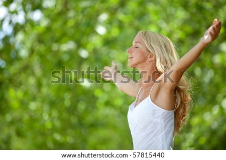 Beautiful girl outdoors feeling the wind with arms open - stock photo