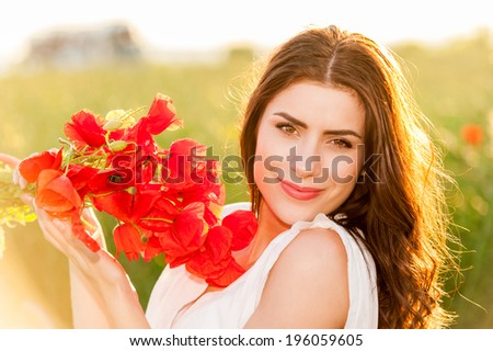 Beautiful Girl over Sky and Sunset in the field holding a poppies bouquet, smiling. Freedom concept. Series. Free Happy Woman Enjoying Nature