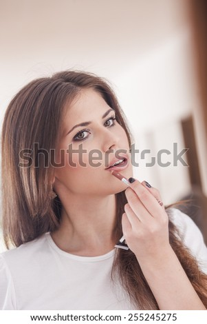 Beautiful girl paints lips in front of a mirror