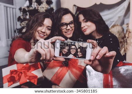 Beautiful girl photographed themselves on the phone on the background of Christmas gifts. Decorative vintage apartment. - stock photo