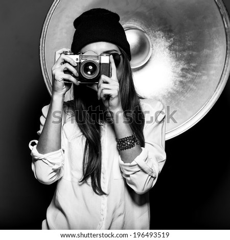 Beautiful girl photographer in hat in the studio with a camera - stock photo
