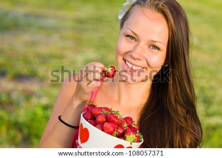 Beautiful girl pick up a strawberry from a bowl, focus on the eyes, landscape image - stock photo