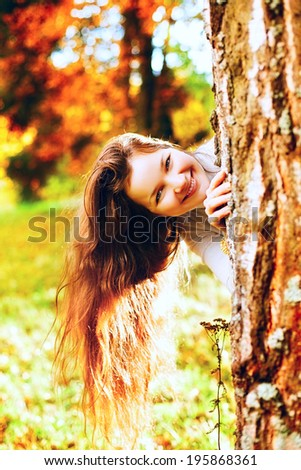 beautiful girl playing and hide for tree in autumn park
