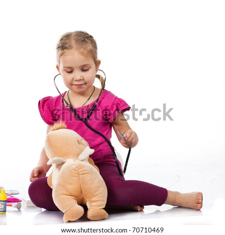 Beautiful girl playing doctor with a doll isolated on white - stock photo