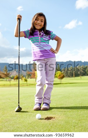 Beautiful girl playing golf looking very happy - stock photo