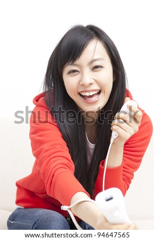 beautiful girl playing video game on sofa - stock photo
