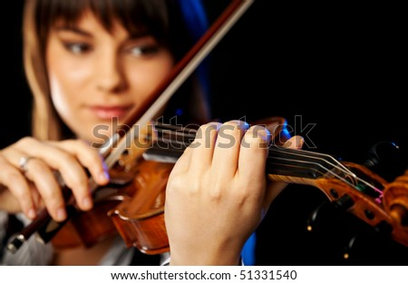 beautiful girl playing violin, selective focus on the front hand
