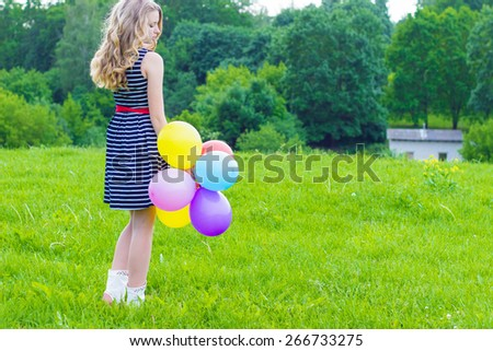 beautiful girl playing with colorful balloons in the summer day - stock photo