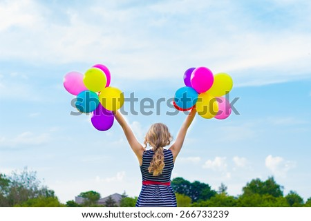 beautiful girl playing with colorful balloons in the summer day against the blue sky - stock photo