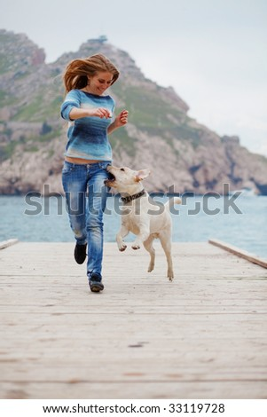 Beautiful girl playing with her dog on berth near sea - stock photo
