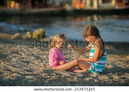 beautiful girl playing with her younger sister with Down syndrome on the beach - stock photo