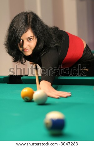 Beautiful girl plays pool in pub and enjoys nightlife - stock photo