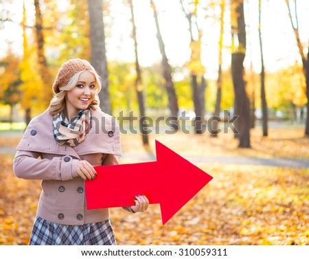 Beautiful girl pointing a direction in autumn. - stock photo