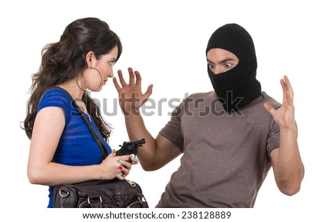 beautiful girl pointing gun at surprised masked male thief isolated on white - stock photo