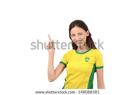 Beautiful girl pointing up. Attractive girl with Brazilian flag on her yellow  t-shirt. Isolated on white. - stock photo