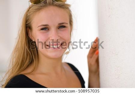 Beautiful girl posing beside the pillars of the Helsinki Cathedral, she looks towards camera - stock photo