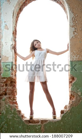 Beautiful girl posing fashion in a window frame. Pretty young woman posing into old wall. Very attractive blonde girl with a transparent white short dress. Silhuette of a romantic young woman posing - stock photo