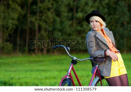 beautiful girl posing in a field with a bicycle