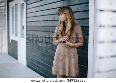 beautiful girl posing on a background of a wooden wall - stock photo