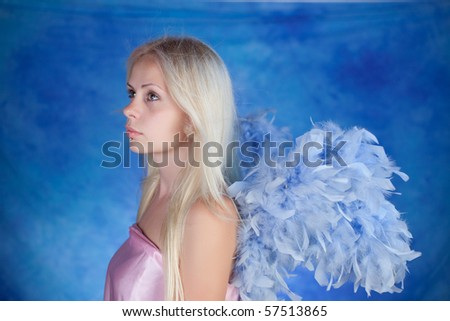 Beautiful girl posing on a blue background - stock photo