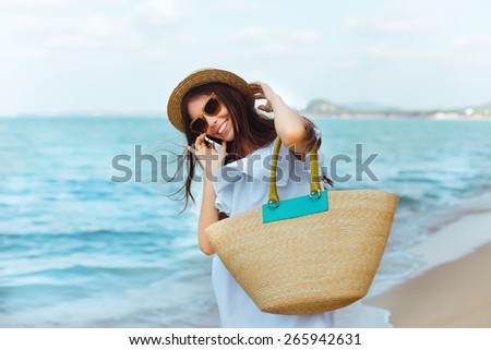 Beautiful girl posing on the beach in the hot sun, with phone,outdoor portrait.Talking with her friends. smiling. - stock photo