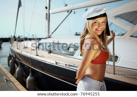 Beautiful girl posing with a yacht on sunny day - stock photo