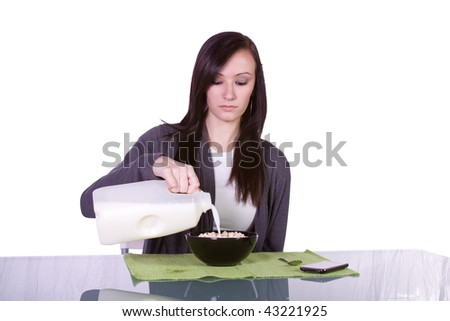 Beautiful Girl Pouring Milk to a Cereal Bowl with her cell phone on the table - Isolated - stock photo