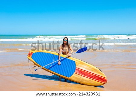Beautiful girl practicing Stand Up paddle board - stock photo