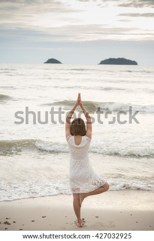 Beautiful Girl Practicing Yoga on The Beach. Relax and yoga. Freedom Concept