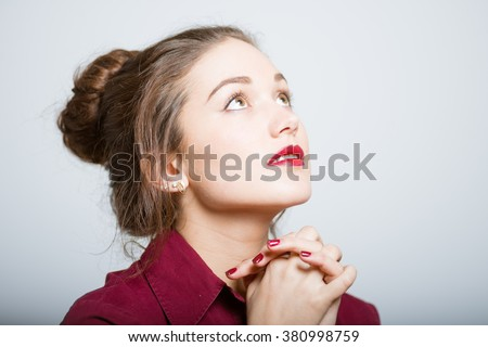 Beautiful girl praying isolated on gray background - stock photo