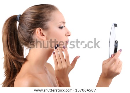Beautiful girl preens before small mirror isolated on white - stock photo