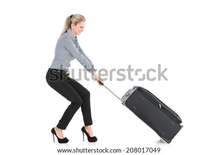 beautiful girl pulling big luggage. side view of young girl on white background - stock photo