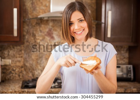 Beautiful girl putting butter on some toast and enjoying it for breakfast - stock photo