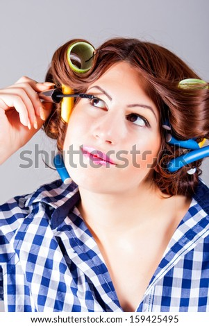 beautiful girl putting on eyeliner - stock photo
