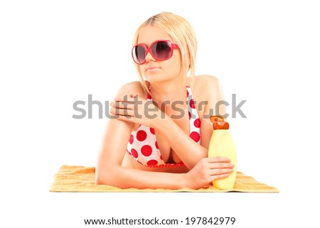 Beautiful girl putting on sunscreen and lying on a towel isolated on white background - stock photo