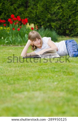 Beautiful girl reading a book  and relaxing in a garden - stock photo