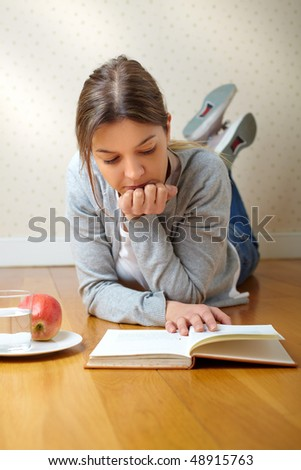 beautiful girl reading a book and smiling on the floor - stock photo