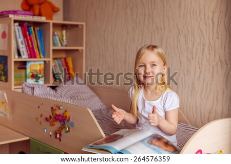 beautiful girl reading a book in the children's room - stock photo