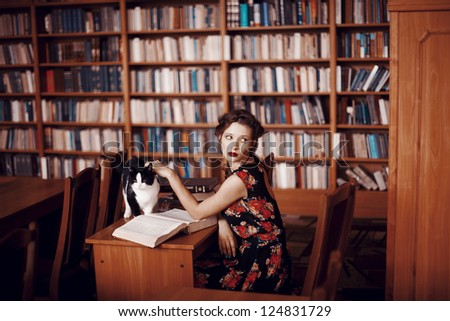 Beautiful girl reading a book in the library, next to the cat - stock photo