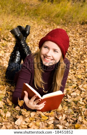 beautiful girl reading a book in the park - stock photo